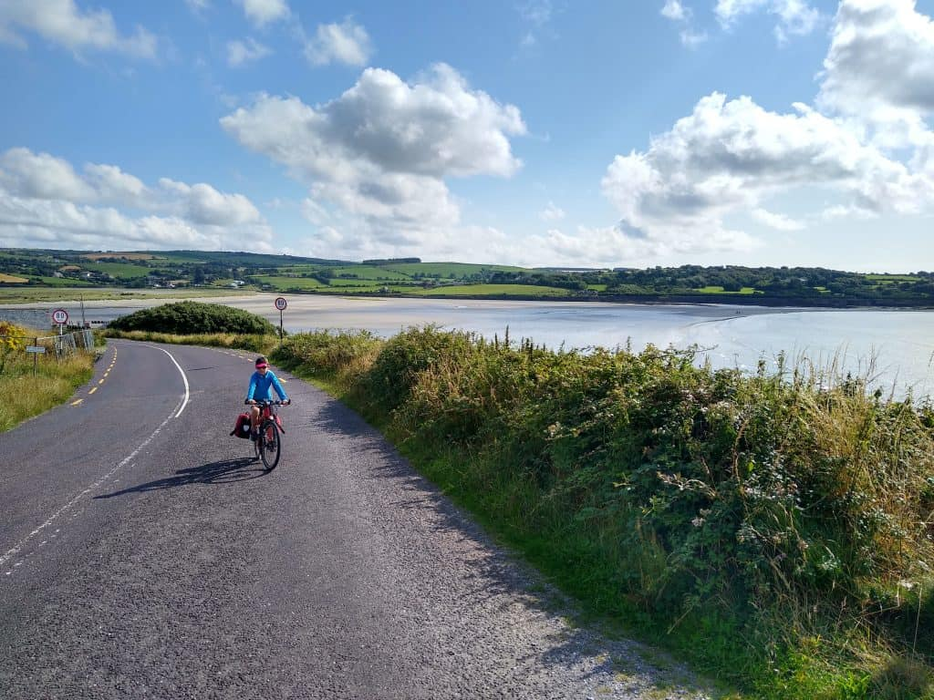 Cycling on a coast road with sea and sandy bay in background